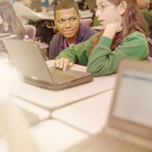 Instructor looks on as student uses a laptop