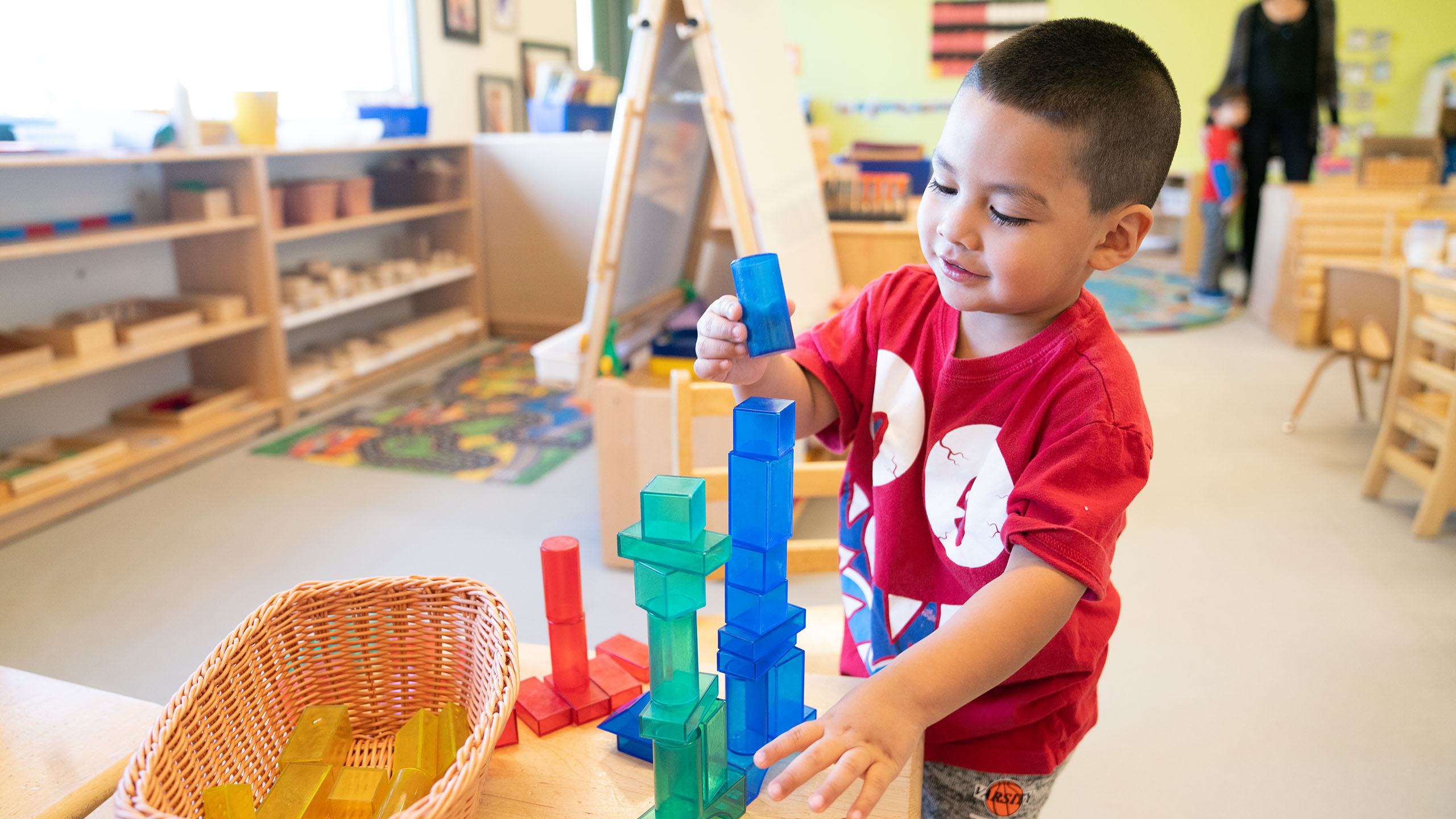 A child gleefully stacks translucent colored blocks